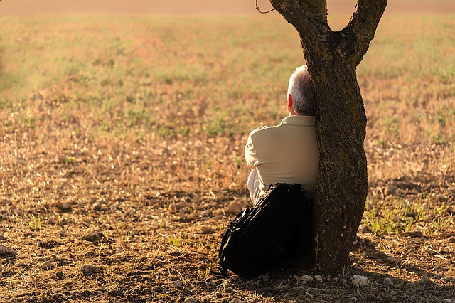 solitary man relaxing against tree