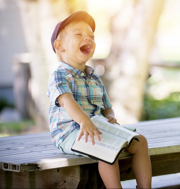 boy laughing with book on his knee