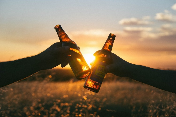 beer bottles being tapped as a celebratory toast with setting sun in background