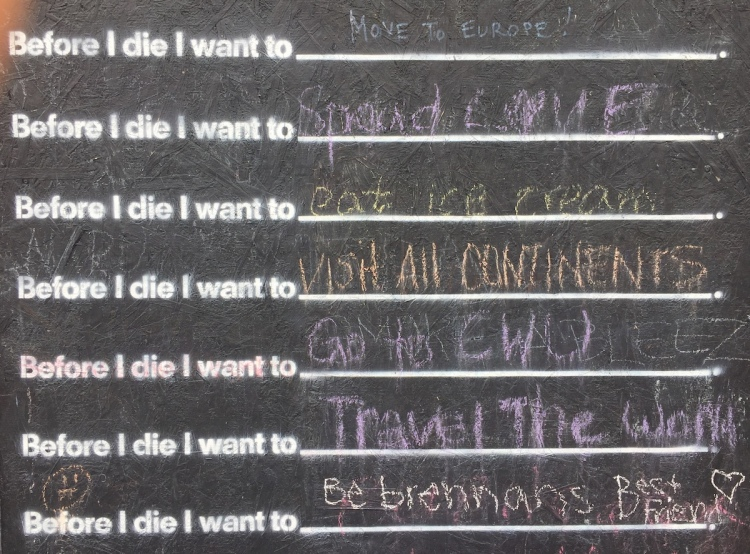 Community chalkboard with the prompt 'Before I die, I want to...'